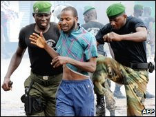Guinean police arrest a protester on September 28, 2009 in front of the biggest stadium in the capital Conakry