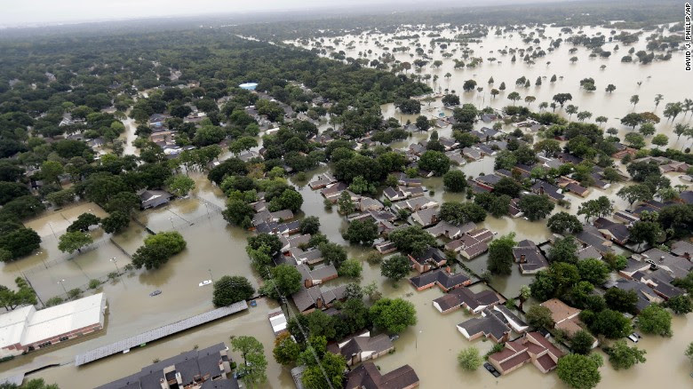 Water from the Addicks Reservoir flows into neighborhoods in Houston as floodwaters rise Tuesday, August 29.