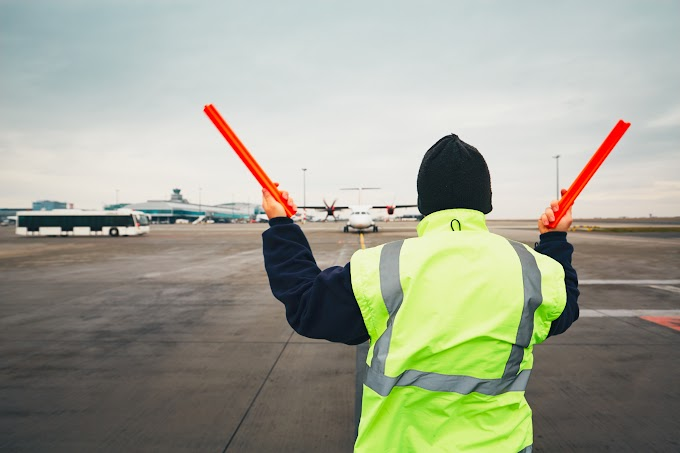 TREND ESSENCE: Airline ground crew in Florida holds up signs thanking customers as nearly empty plane prepares to take off