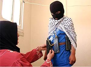 Em um dos sites, uma imagem de uma mão colocando um cinto de explosivos em seu filho, incentivando o uso de crianças em ataques