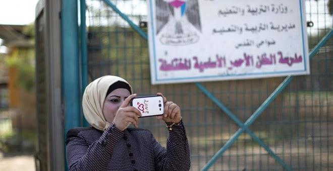 Una mujer hace una foto en el colegio de la comunidad de Jan al Ahmar. EFE/Atef Safadi