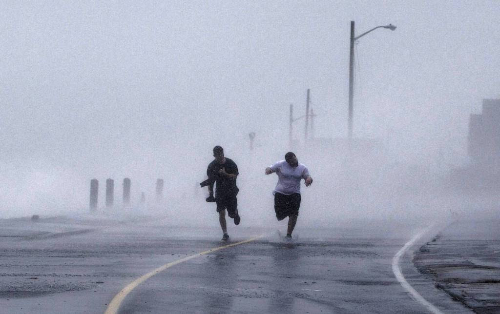 Two boys run down Foster Avenue while dodging high winds and waves from the effects of Hurricane Sandy in Marshfield, Massachusetts. The monster storm bearing down on the East Coast, strengthened on Monday after hundreds of thousands moved to higher ground.