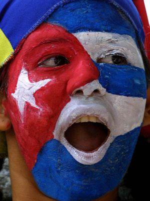 Una mujer con la cara pintada de la bandera cubana frente a la embajada de Cuba en Venezuela.