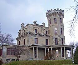 Uma casa com uma torre de cinza no lado direito e uma asa da esquerda.