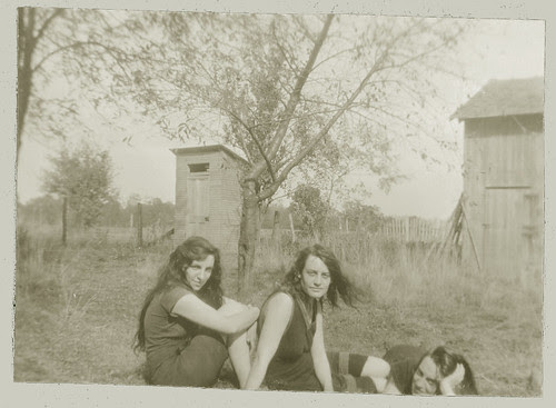 Three girls posing in front of the outhouse