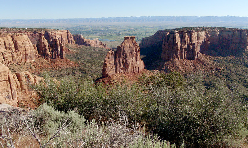 Monument Canyon is home to Independence Monument (a monolith or tower), Colorado National Monument.  In the upper  background, the Bookcliffs rise above the Grand Valley.