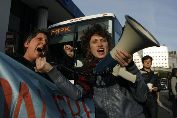 Sara Shortt, left, from the Housing Rights Committee of San Francisco and activist Erin McElroy, right, block a Facebook bus in San Francisco heading to Menlo Park. Bay Area protests against the tech industry escalated on Wednesday when activists showed up on the doorstep of a Google employee. (Liz Hafalia / San Francisco Chronicle / January 22, 2014)