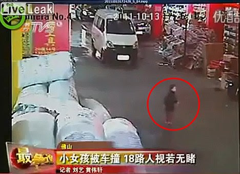 Unaware: Video footage shows the little girl crossing the road at Guangfo Hardware Market, without spotting the van approaching
