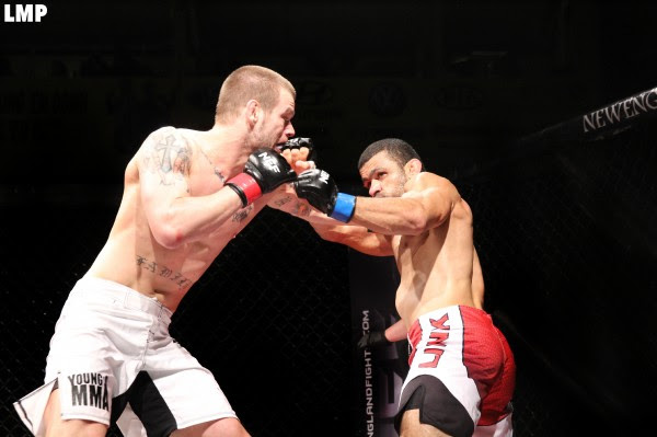 Ryan Sanders (left) of Brewer battles Gil de Freitas of Ludlow, Massachusetts, during a mixed martial arts title bout on the New England Fights XIII card Saturday night at the Androscoggin Bank Colisee.