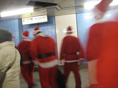 Santas arriving at Embankment Tube - Santacon 2011