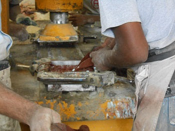 The colored cement is hand-poured into the different sections of the molds.