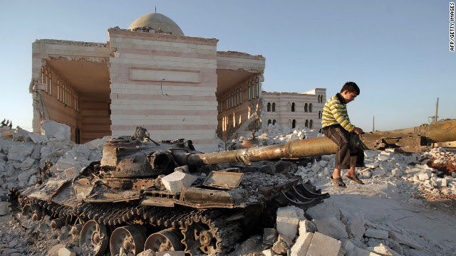 A boy plays on the gun of a destroyed Syrian army tank partially covered in the rubble of the destroyed Azaz mosques, north of the restive city of Aleppo, on Thursday, August 2.