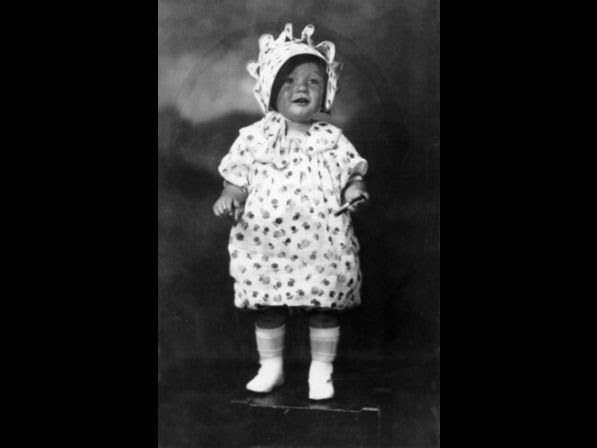 Monroe (born Norma Jean Mortenson in 1926) at the age of two, standing on a box in a floral print dress and matching bonnet.