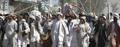 Protestors walk with sticks, as they carry a wounded colleague during a demonstration to condemn the burning of a copy of the Muslim holy book by a Florida pastor, in Kandahar, Afghanistan on Saturday, April 2, 2011. (AP Photo/Allauddin Khan)