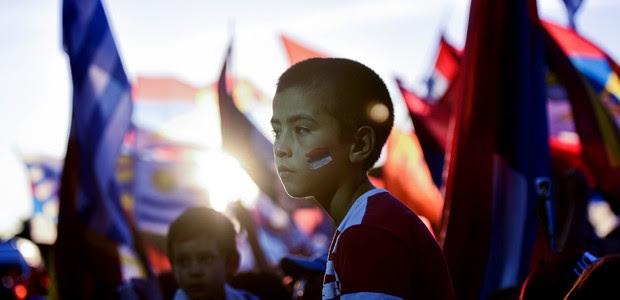 Menino escuta discurso do candidato favorito à Presidência uruguaia, Tabaré Vazquez, durante o encerramento da campanha em Montevideu, na quinta-feirra (27) (Foto: Matilde Campodonico/AP)