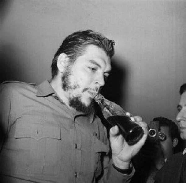 Ernesto Che Guevara, na época Ministro da Indústria cubano, bebendo Coca-Cola, em 1961, em Punta del Este, no Uruguai.    Che Guevara, um dos líderes da Revolução Cubana, foi flagrado bebendo o refrigerante considerado como o símbolo do capitalismo e do imperialismo estadunidense, durante um dos intervalos da Conferência Econômica e Social Inter-América, em agosto daquele ano.    Autor da foto: Desconhecido.  Texto de Diego Vieira