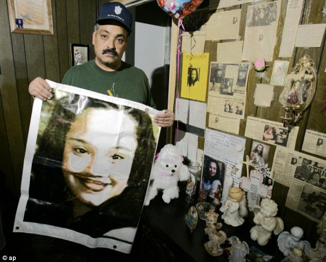 Distraught: Felix DeJesus, holding a banner showing his daughter's photograph, standing by a memorial in his living room in Cleveland (file photo)