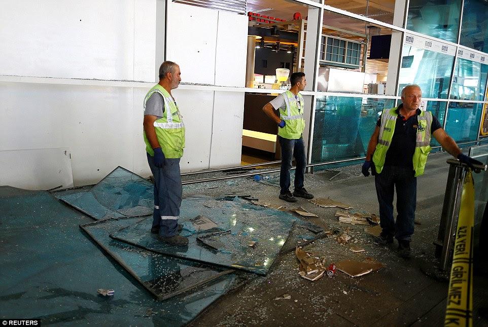 A operação de limpeza começa no aeroporto Ataturk com vidro como quebrado e detritos encontra-se na calçada em torno do edifício do terminal