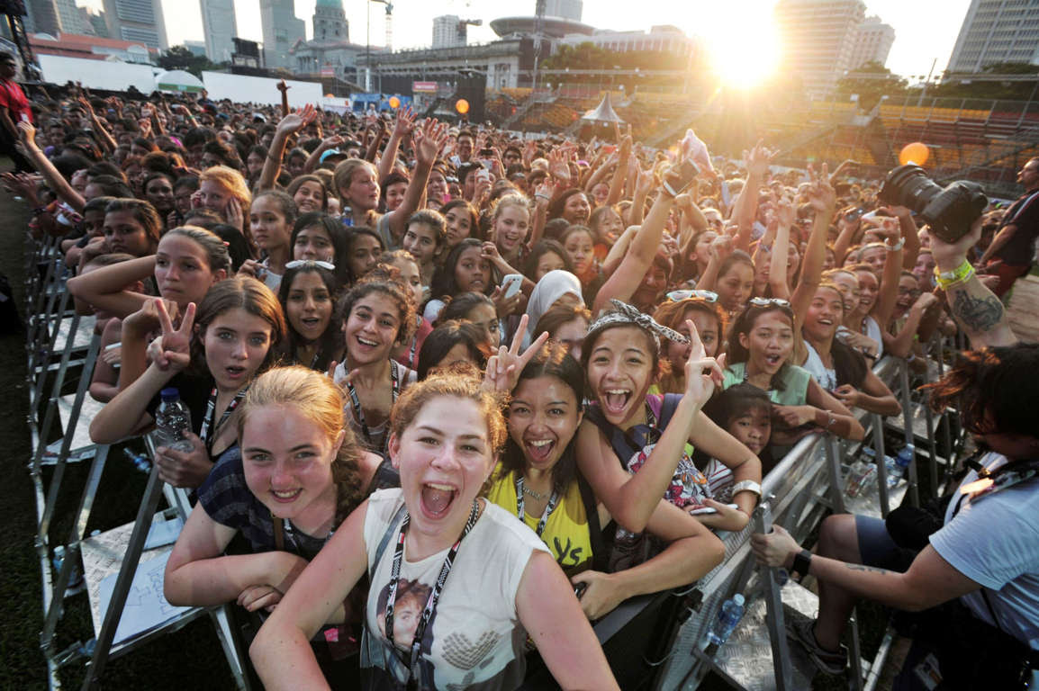 Fans smile at a photographer as American singer-songwriter Adam Young performs during a closing concert in Singapore Monday, Sept. 23, 2013, a day after the Singapore Formula One Grand Prix. (