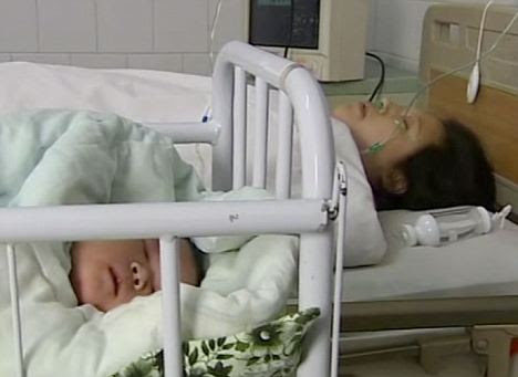 Sleeping peacefully: Chun Chun rests beside mother Wang Yujuan, who said the size of her belly told her she was due a big baby