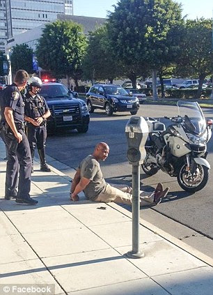 Detained and cuffed: Charles Belk sits on the street with his legs crossed while two officers guard him after his arrest for a crime he did not commit on Friday
