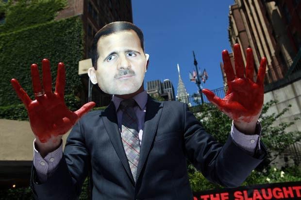 Manifestante com máscara do presidente sírio Bashar al Assad protesta contra o regime, nesta quinta-feira (7), em frente à sede da ONU em Nova York (Foto: AFP)