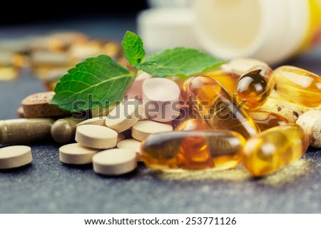 pills and multivitamins on a dark background, closeup - stock photo