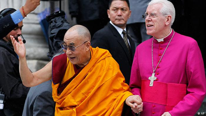 Dalai Lama, Tibetan Buddhist spiritual leader, left, with St. Paul's Cathedral Canon Pastor Reverend Michael Colclough, right, waves as he arrives at St. Paul's Cathedral in London to receive the 2012 Templeton Prize awarded to him for encouraging scientific research and harmony among religions, Monday, May 14, 2012. (Foto:Sang Tan/AP/dapd)