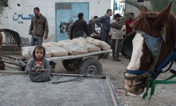 Nine-year-old Adham scrapes up concrete dust into his bag to sell as men haggle in the background over the price of a cart of black-market concrete.