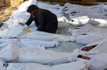 Un hombre sostiene el cuerpo de un niño entre decenas de muertos por un ataque químico del régimen, según la oposición, cerca de Damasco.