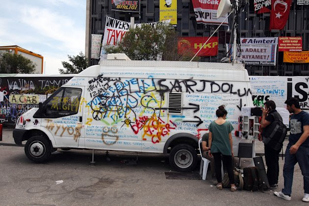 Protesters use a mobile station of a telecommunication company to charge their cellphones near a van covered with anti-government signs at the Taksim square in Istanbul Saturday, June 8, 2013. Prime Minister Erdogan prepared to convene his party leadership Saturday as anti-government protests enter their ninth day, with thousands of people still occupying Istanbul's central Taksim Square. (AP Photo/Thanassis Stavrakis)