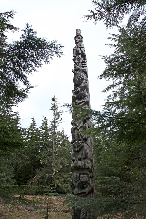 a totem pole among the trees in the Totems Historic District, Kasaan, Alaska