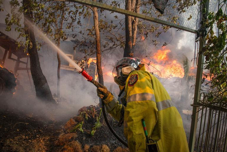 This handout photo taken on January 12, 2014 and supplied by Australia's Department of Fire and Emergency Services (DFES) shows a firefighter working to contain wildfires in the Stoneville area, a suburb near Perth in Western Australia
