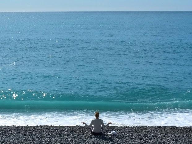 Mulher medita na praia, em Nice. (Foto: Lionel Cironneau/AP)