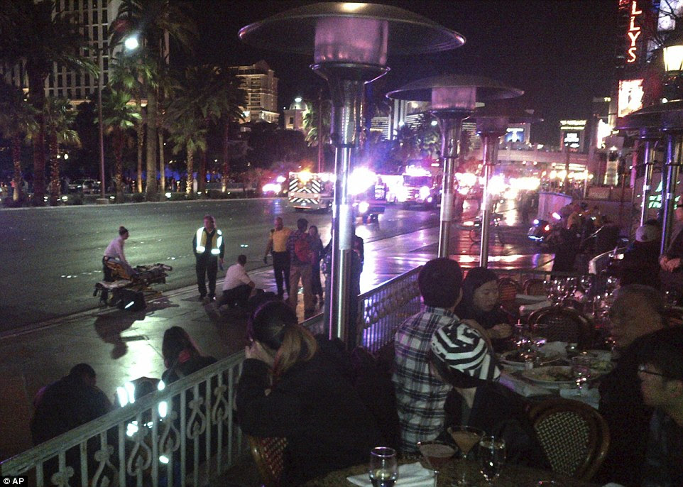 People crowd a sidewalk while police cars and ambulances gather on a street after a car drove onto a busy sidewalk and mowed down people outside a casino in Las Vegas