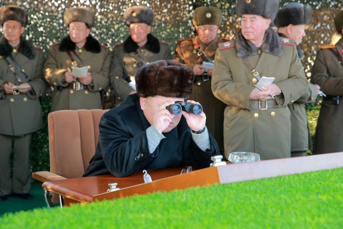Kim Jong-un looks through binoculars while surrounded by North Korean officials