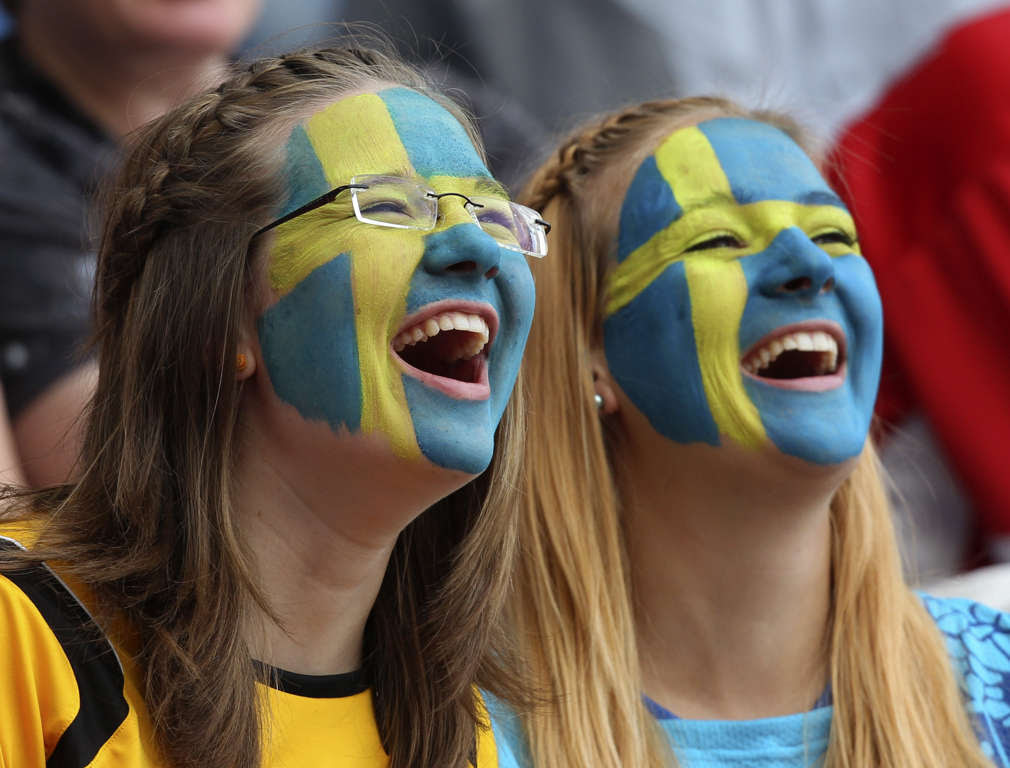 Fans with faces painted in Sweden colors laugh prior to the match for third place between France and Sweden at the Women's Soccer World Cup in Sinsheim, Germany, Saturday, July 16, 2011. (AP