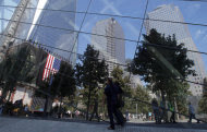 Visitor are reflected in the windows of the 9/11 museum as they stroll the grounds of the 9/11 memorial plaza in the World Trade Center site in New York Monday, Sept. 12, 2011, on the first day that the memorial was opened to the public. (AP Photo/Mike Segar, Pool)