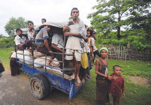 Rohingya sit in a tractor loaded with bags of donated rice outside a temporary relief camp on the outskirts of Sittwe in June. Photo: AFP