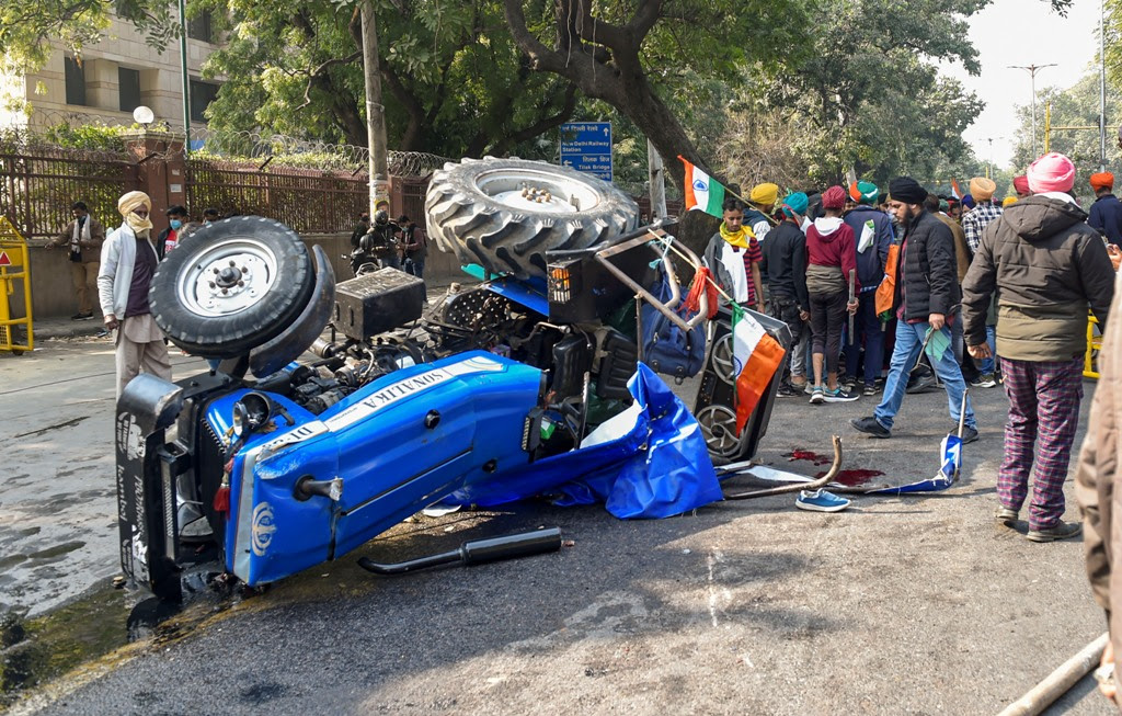 New Delhi: Farmers stand next to an overturned tractor at ITO during their Kisan Gantantra Parade to protest against Centres farm reform laws, on the occasion of 72nd Republic Day, in New Delhi, Tuesday, Jan. 26, 2021. A protesting farmer died after his tractor overturned at Central Delhis ITO. (PTI Photo/Ravi Choudhary)(PTI01 26 2021 000323B)