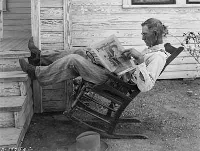 An old farmer reads a farming magazine