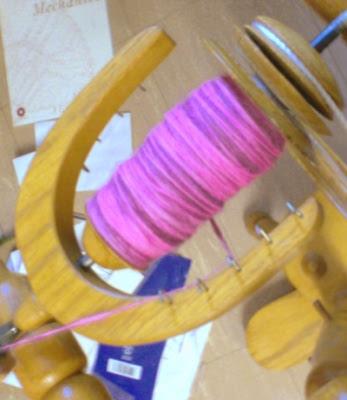 Full spinning wheel bobbin of pink Rambouillet handspun wool yarn