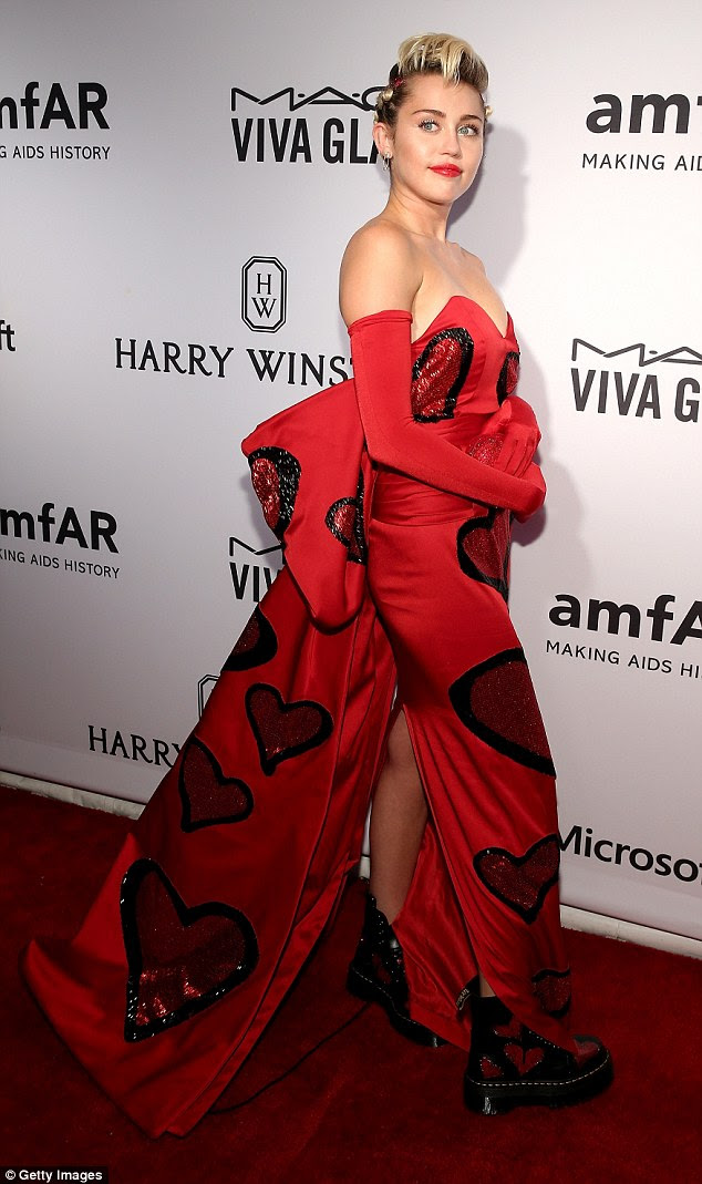 Red-dy to party! Miley showed off her heart-detailed gown paired with matching combat boots