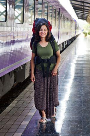 Um jovem mochileiro andando em uma estação ferroviária.
