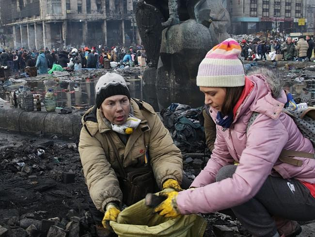 Cleaning up ... protesters Olya Omlukh, 21, and her mum Svetlana help cleaning up after a