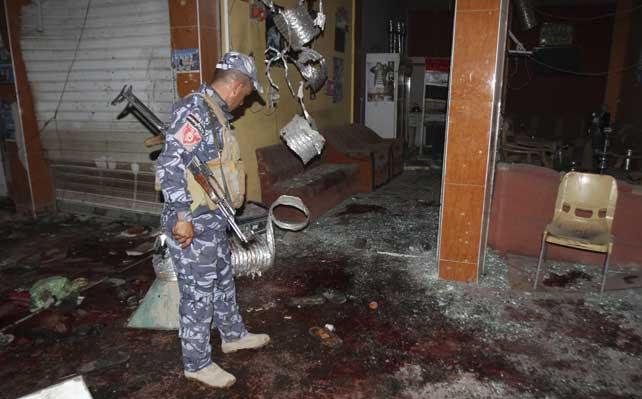 Un policía observa los efectos de la explosión en una tetería de la ciudad de kirkuk.