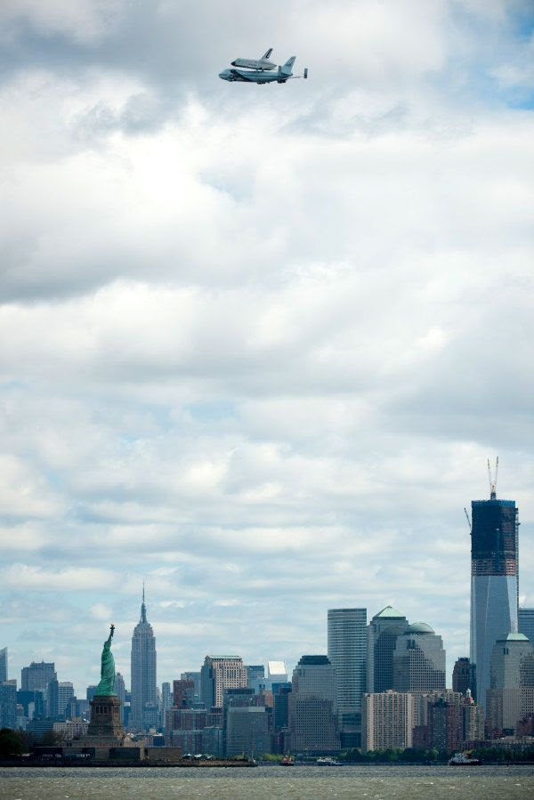 With the Statue of Liberty, Empire State Building and 1 World Trade Center down below, the shuttle Enterprise and NASA 905 fly over New York City on April 27, 2012.