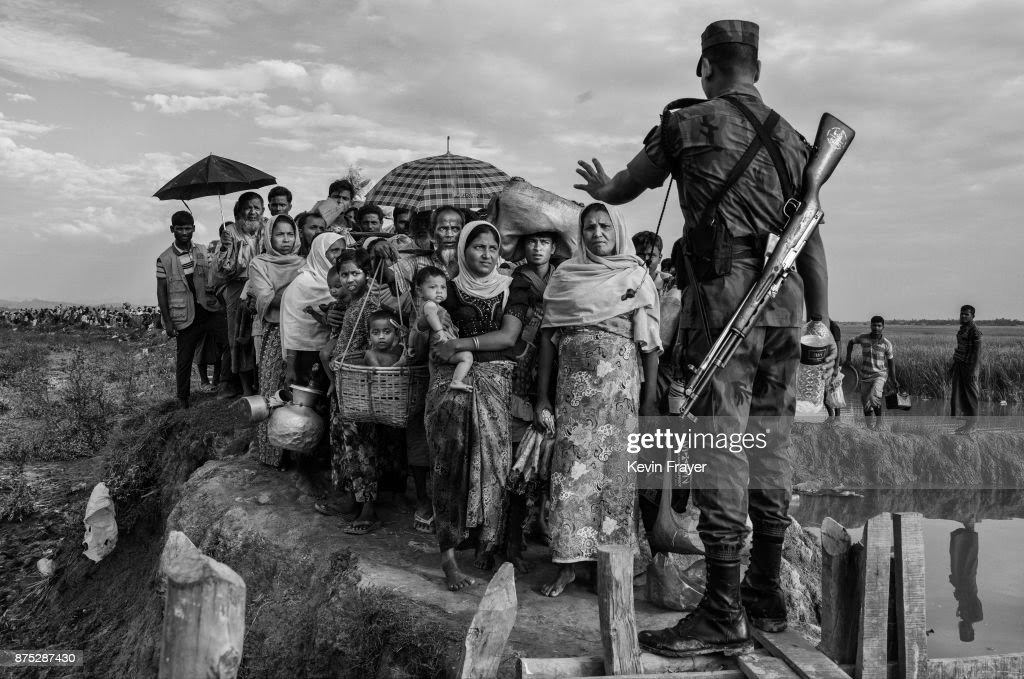 COX'S BAZAR, BANGLADESH - NOVEMBER 02: A Bangladeshi border guard from the BGB gestures as he controls a crowd of Rohingya Muslim refugees waiting to proceed to camps after crossing the border from Myanmar into Bangladesh near the Naf River on November 2, 2017 near Anjuman Para in Cox's Bazar, Bangladesh. More than 600,000 Rohingya refugees have flooded into Bangladesh to flee an offensive by Myanmar's military that the United Nations has called 'a textbook example of ethnic cleansing'. The refugee population continues to swell further, with thousands more Rohingya Muslims making the perilous journey on foot toward the border, or paying smugglers to take them across by water in wooden boats. Hundreds are known to have died trying to escape, and survivors arrive with horrifying accounts of villages burned, women raped, and scores killed in the 'clearance operations' by Myanmar's army and Buddhist mobs that were sparked by militant attacks on security posts in Rakhine state on August 25, 2017. What the Rohingya refugees flee to is a different kind of suffering in sprawling makeshift camps rife with fears of malnutrition, cholera, and other diseases. Aid organizations are struggling to keep pace with the scale of need and the staggering number of them - an estimated 60 percent - who are children arriving alone. Bangladesh, whose acceptance of the refugees has been praised by humanitarian officials for saving lives, has urged the creation of an internationally-recognized 'safe zone' where refugees can return, though Rohingya Muslims have long been persecuted in predominantly Buddhist Myanmar. World leaders are still debating how to confront the country and its de facto leader, Aung San Suu Kyi, a Nobel Peace Prize laureate who championed democracy, but now appears unable or unwilling to stop the army's brutal crackdown.