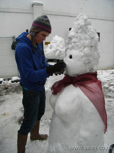 Man carving nose of snow-woman with knife