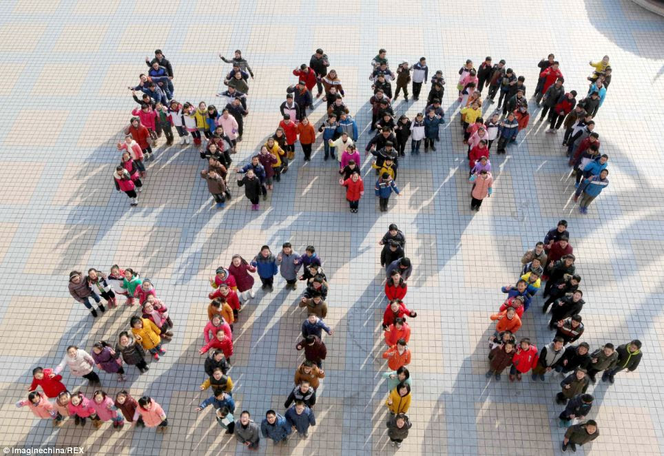 Young Chinese students at a middle school in Hanshan county, Anhui province, line up to form 'Happy 2014' to celebrate the New Year